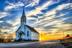 A,lone,wooden,church,at,dusk,with,sunset,clouds,in